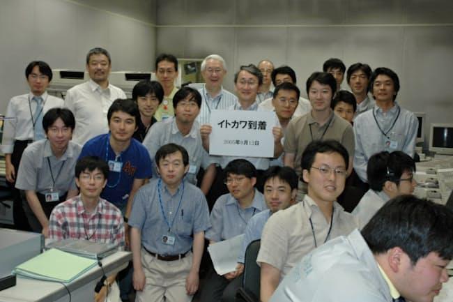 はやぶさのイトカワ到着を喜ぶプロジェクトチーム(ボードを持つのが川口氏)=JAXA提供